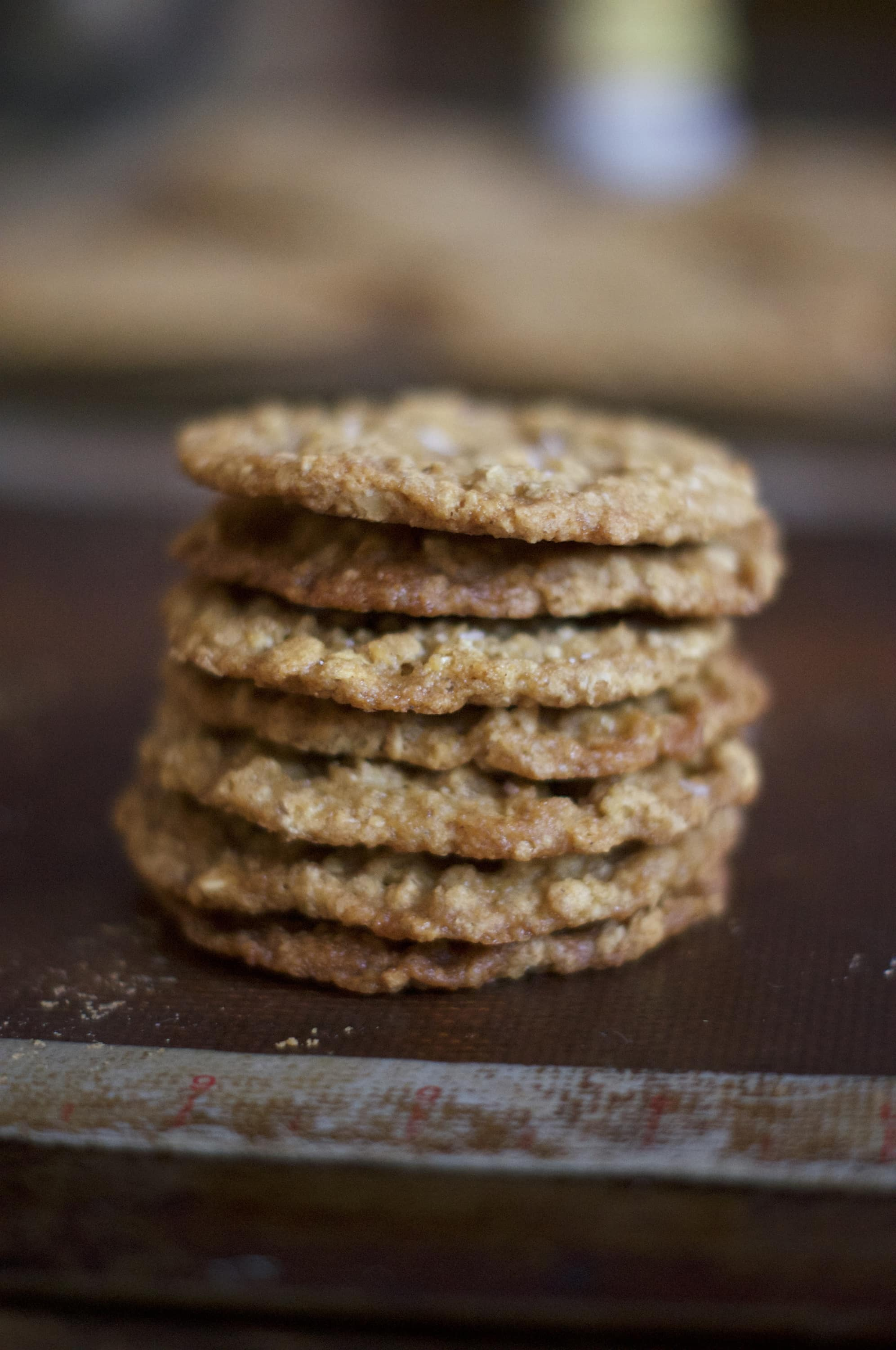 A stack of oatmeal lace cookies sits on a baking tray