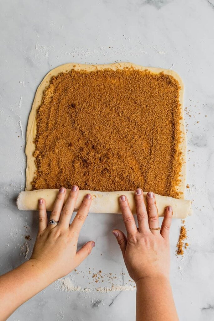 Hands roll up the filled dough for overnight cinnamon rolls recipe.