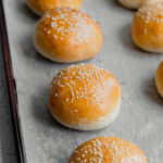Brioche Burger Buns lined up on a parchment lined baking sheet
