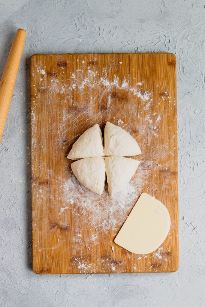 naan dough cut into four equal pieces on a wooden cutting board