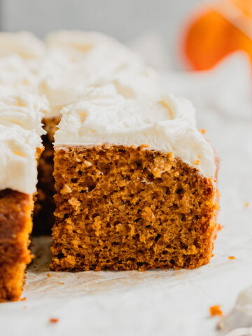 Cream cheese frosted pumpkin bars on a piece of parchment paper.