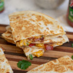 A stack of breakfast quesadillas sit on a wooden cutting board