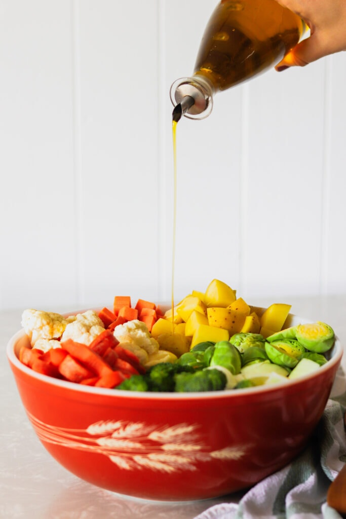 A hand drizzles olive oil over vegetables in a mixing bowl.