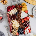 A silver tray is filled with red, white, and blue fruits, cheeses, and crackers to celebrate Fourth of July. There is a tray of crackers in the top right corner and wine glasses in the bottom right and top left.