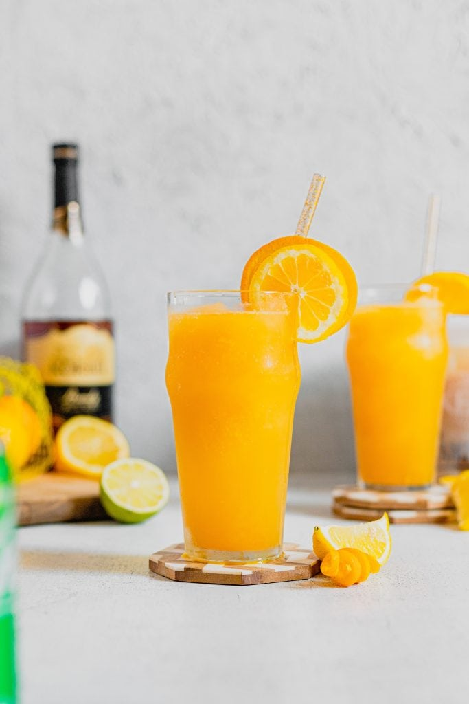 A tall pub glass is filled with brandy slush. The glass sits on a wooden coaster surrounded by citrus fruits. There is a bottle of brandy in the backhand left corner. Another glass of brandy slush is in the backhand right corner. The drinks are garnished with orange and lemon slices.