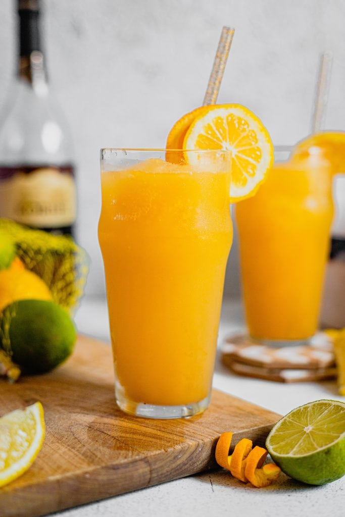 A tall glass if filled with frozen Brandy Slush and is garnished with orange slices and a straw. There is fresh citrus around the glass on a cutting board.