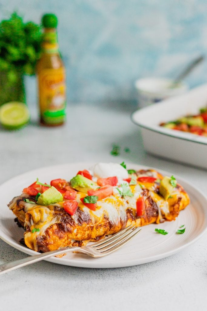 A white plate has two venison enchiladas on it. The plate sits on a white backdrop with a blue background. There are tomatoes, avocados, sour cream, and cilantro on top of the enchiladas.