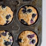 baked blueberry muffins sit in a vintage muffin pan