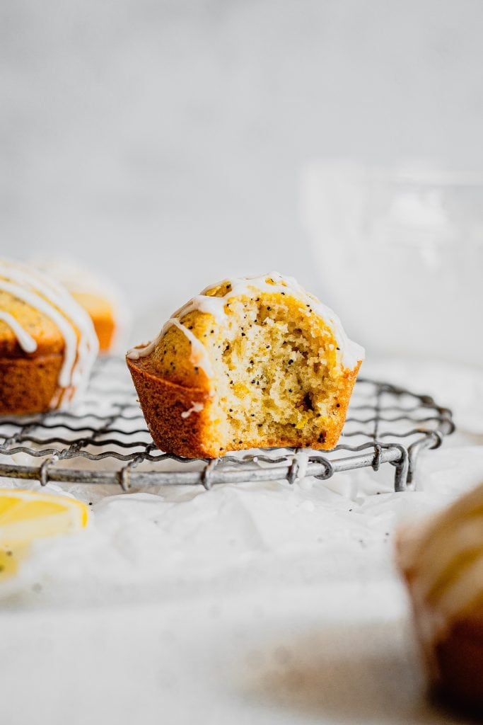 A glazed lemon poppy seed muffin with a bite taken out of it sits on on a round, wire cooling rack.