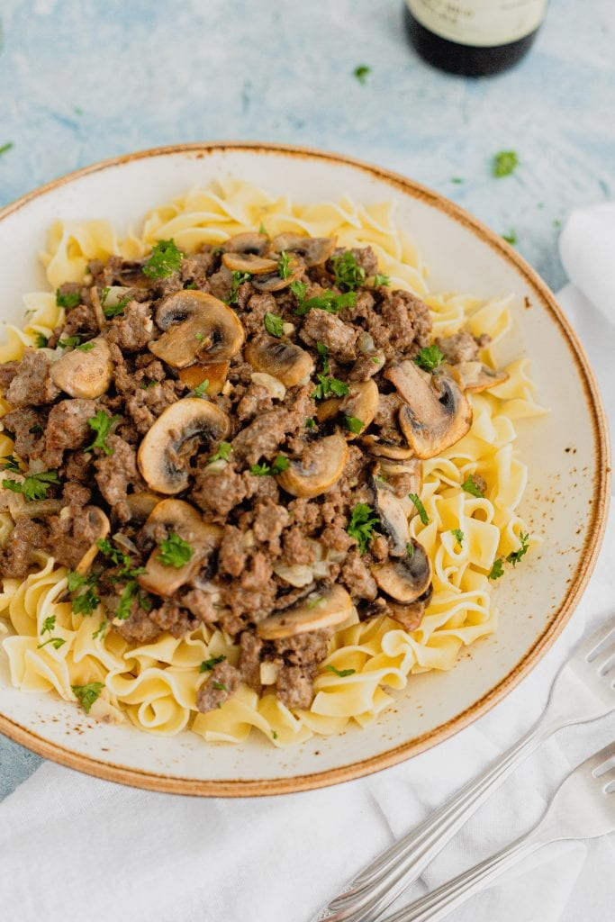 A large white bowl is fill with venison stroganoff. The dish is sprinkled with parsley and sits on a blue backdrop.