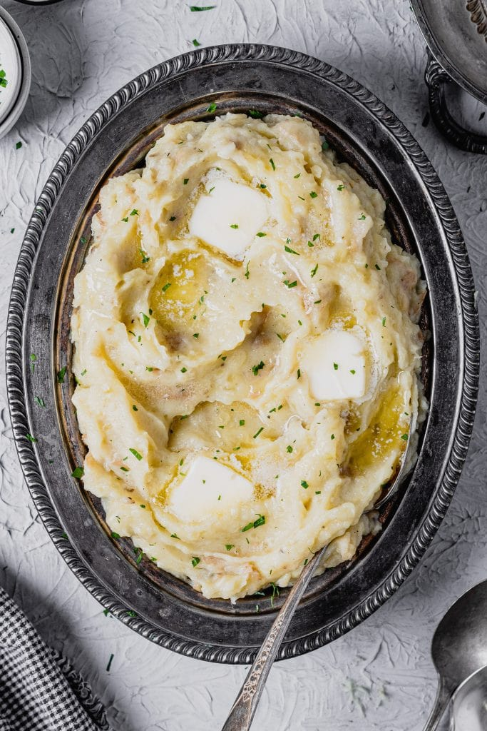 An antique silver serving dish is filled with mashed potatoes. It sits on a textured gray background. There are pads of butter on top of the potatoes and the whole dish is sprinkled with fresh herbs.