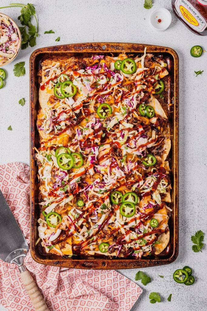 A baking pan is covered in a layer of bbq pulled pork nachos. They are covered in cheese, coleslaw, BBQ sauce and jalapeño slices. There is a spatula and red-patterned towel to the left of the pan.