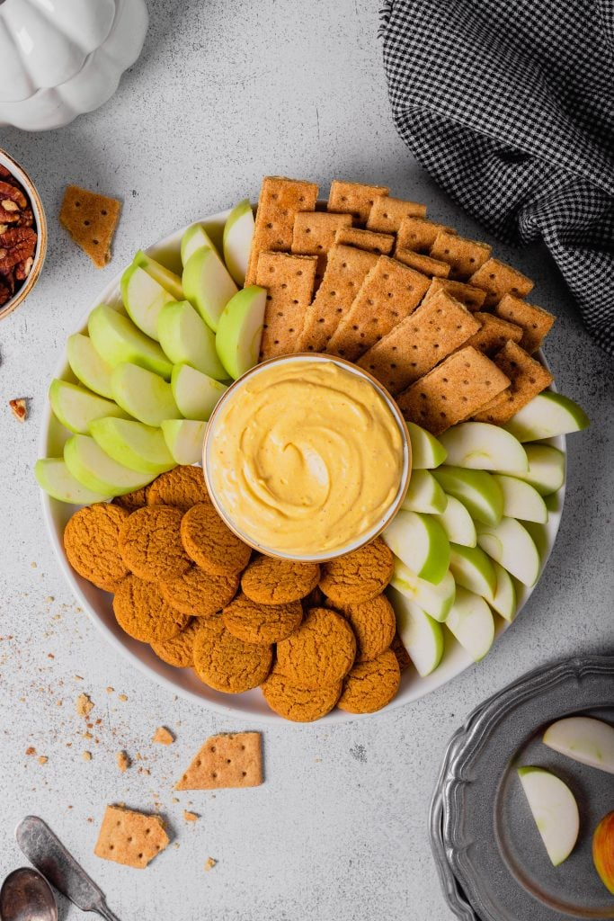 An overhead shot of a bowl of no-bake cheesecake dip surrounded by graham crackers, gingersnap cookies, and apple wedges. Everything is set on a white backdrop.