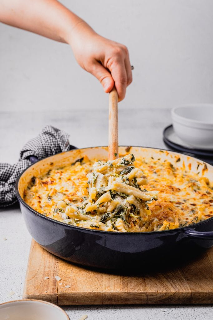 A hand holding a wooden spoon serves a large scoop of spinach and artichoke mac and cheese out of a shallow enamel pot set on a wooden cutting board.