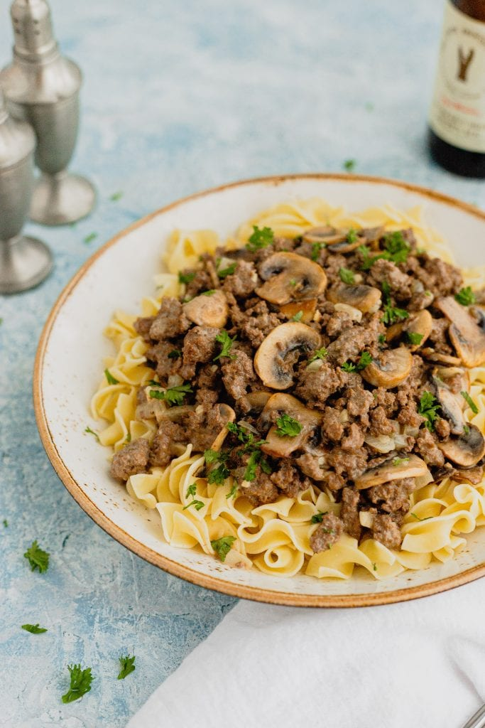 A large white bowl is fill with venison stroganoff. The dish is sprinkled with parsley and sits on a blue backdrop. There are silver salt and pepper shakers and a bottle of beer sitting behind the bowl.
