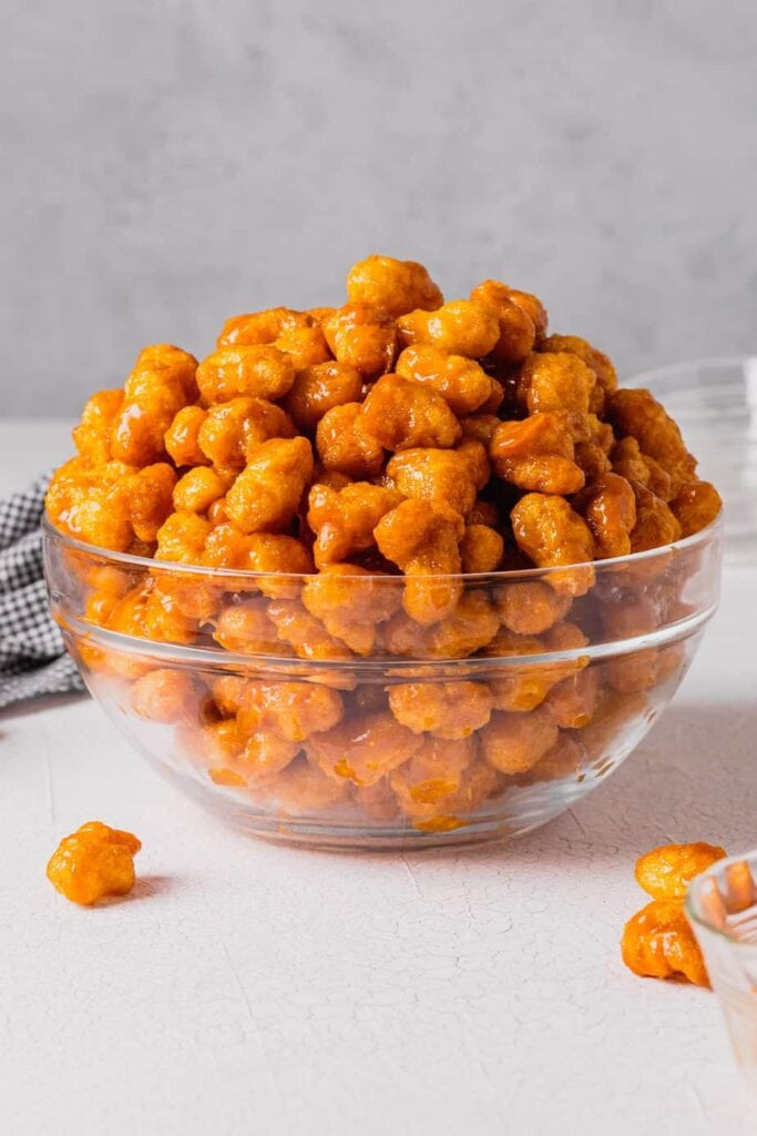 A straight on shot of a large, clear glass bowl filled with puffed caramel corn. The bowl is on a white backdrop and there is a white and black checkered napkin behind the bowl.