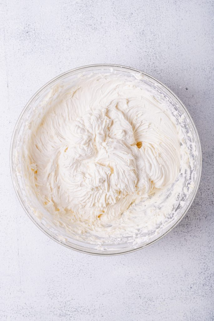 An overhead shot of a large glass bowl filled with a batch of the best cream cheese frosting recipe. The bowl sits on a white speckled backdrop.