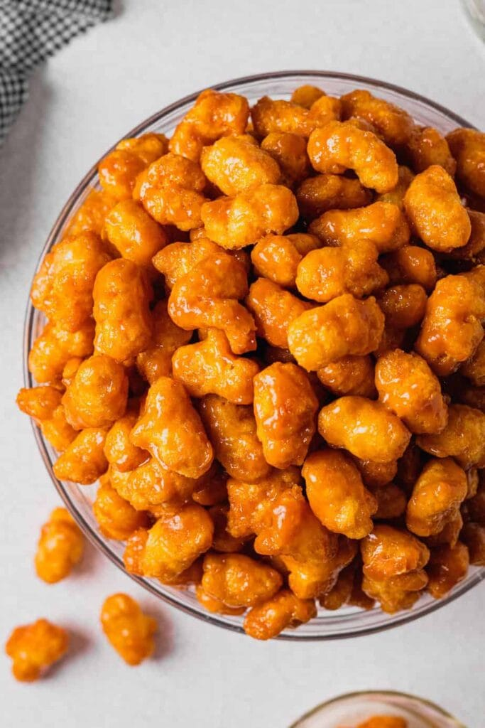 An overhead shot of puffed caramel corn in a large clear glass bowl.