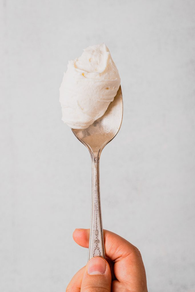 An antique silver spoon with a dollop of cream cheese frosting is held up to the camera.
