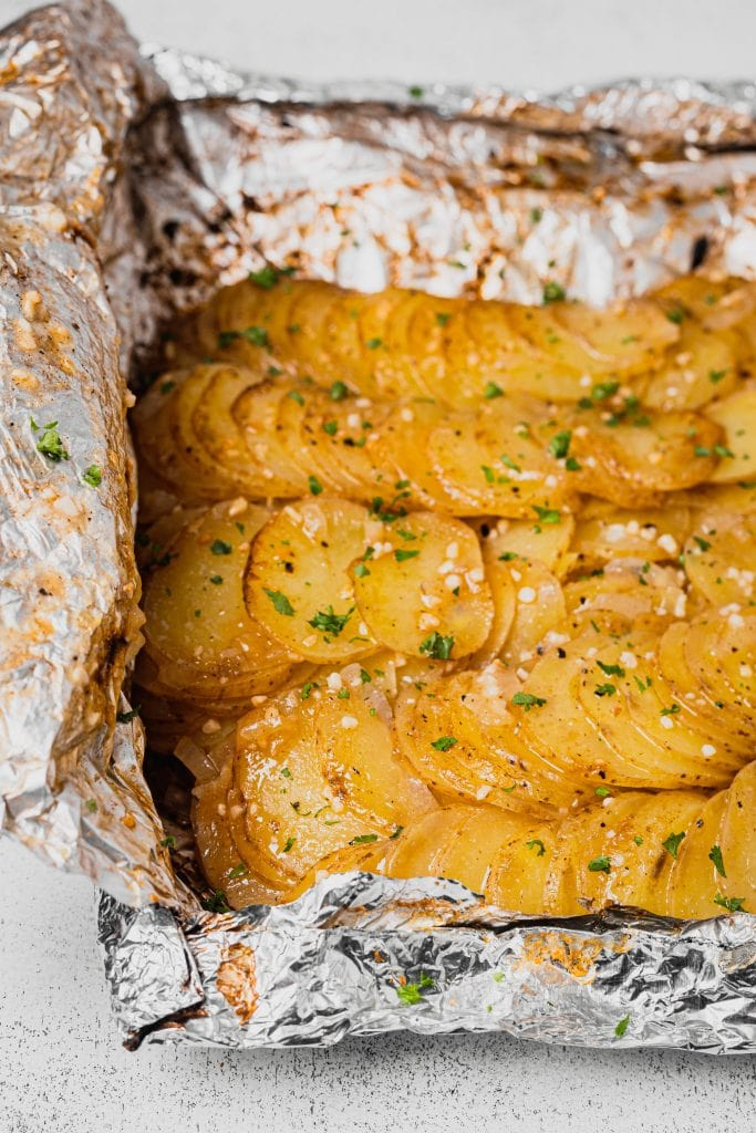 A foil packet filled with grilled potatoes sits on a white and grey speckled backdrop. The potatoes are sprinkled with garlic, onion, and parsley.