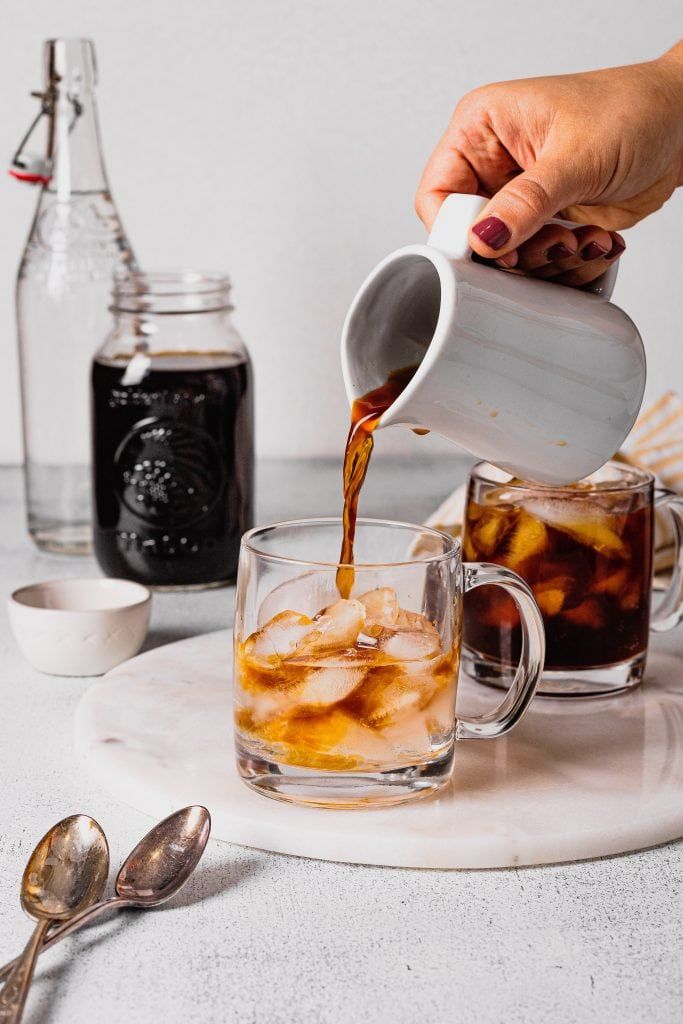 A hand pours cold brew coffee concentrate from a small white pitcher into a clear glass coffee cup filled with ice.