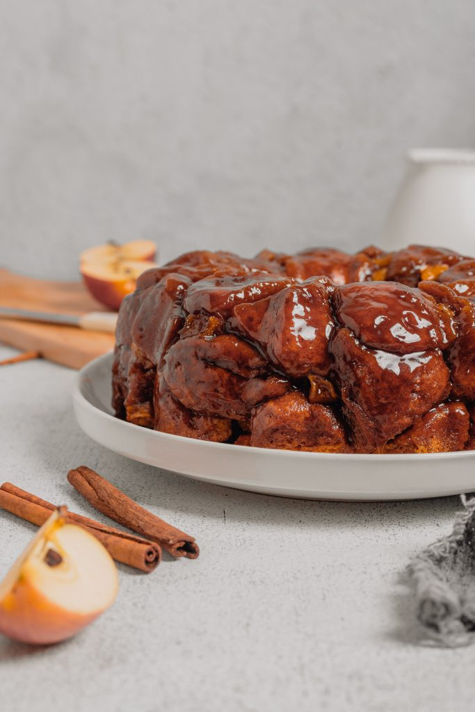 A straight on shot of a large white plate holding a batch of apple cinnamon monkey bread. There is a grey linen in the right hand corner and cinnamon sticks and apple slices in the lefthand corner.