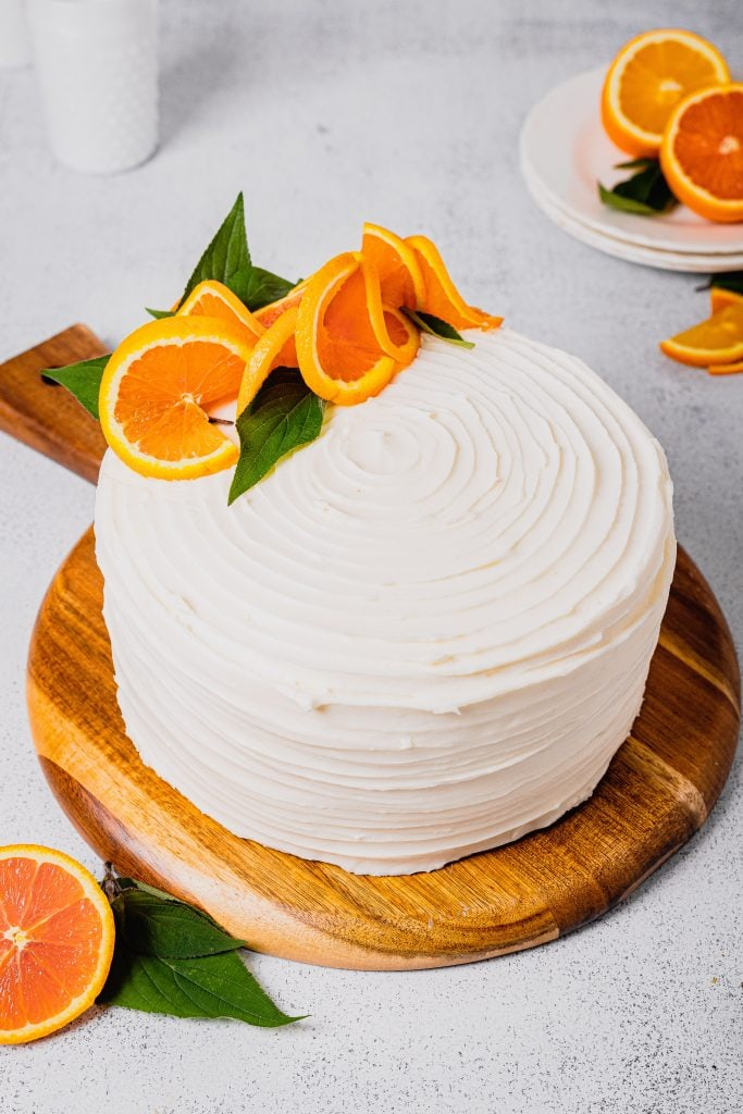 An orange cream cake decorated in fresh orange slices sits on a wooden cutting board on a white backdrop.