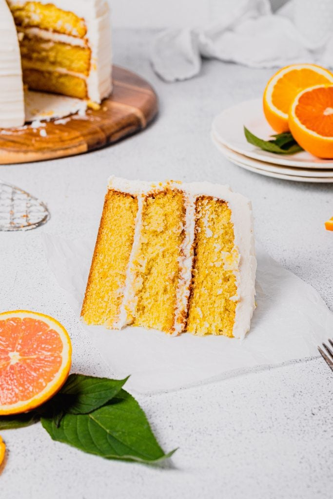 A slice of orange cream layer cake sits on a piece of parchment paper. The rest of the cake is in the background and there are fresh orange slices in the foreground. All on a white background.