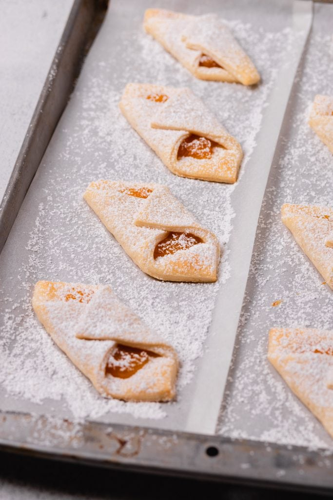 Apricot filled cream cheese cookies sit on a baking tray dusted with powdered sugar.