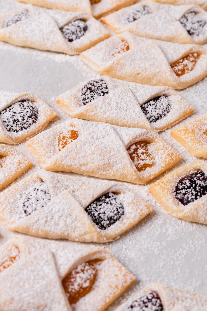 A mixture of apricot and raspberry filling kolaczki cookies are on a piece of parchment paper dusted with powdered sugar.