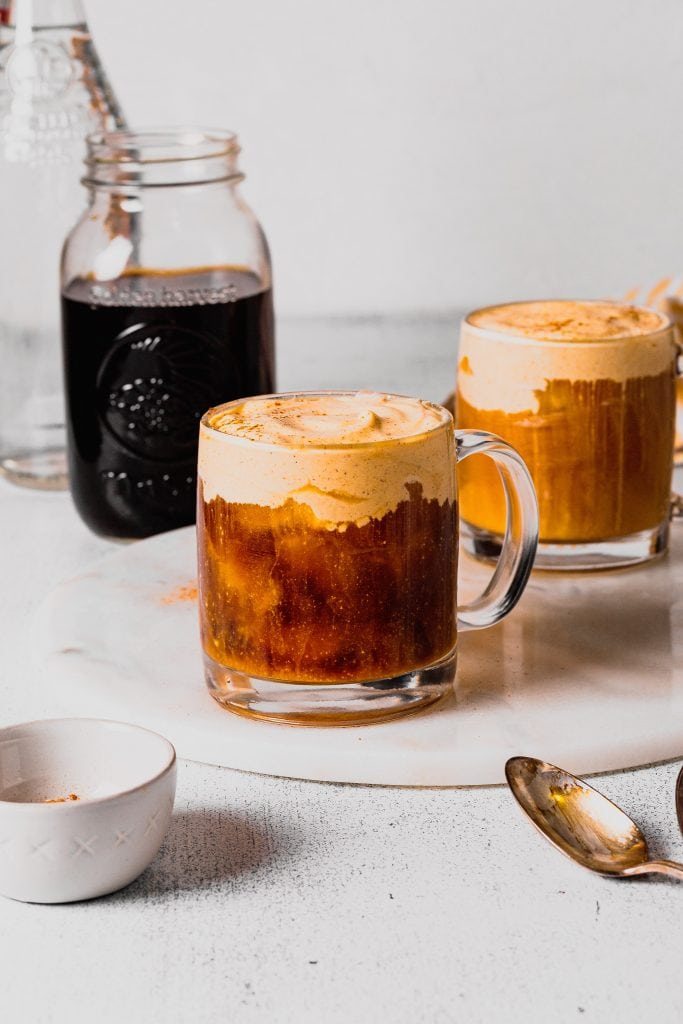 A clear glass coffee cup sits on a white marble tray. The cup is full of cold brew and topped with pumpkin cream cold foam. There is another cup behind it to the right and a jar of cold brew coffee to the left.