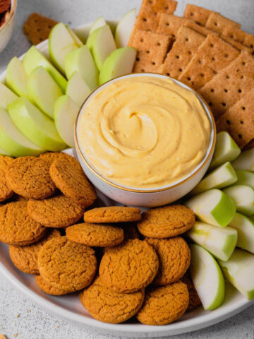 A dish of pumpkin pie cheesecake dip on a platter with fresh apples and graham crackers.