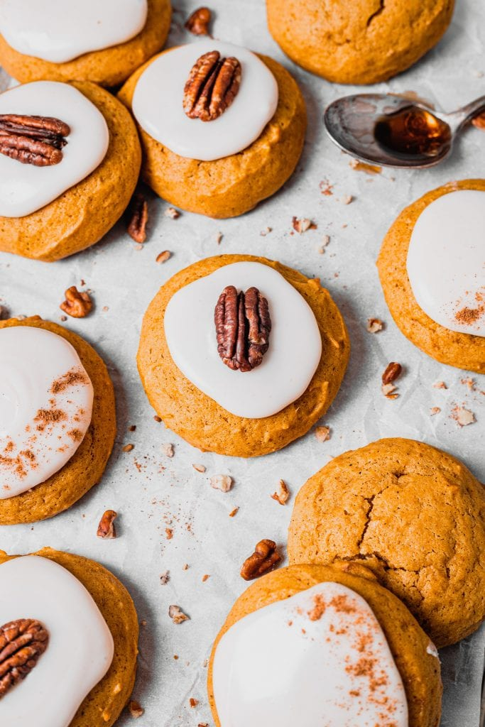A far away shot of a soft pumpkin cookie with maple glaze. The cookie is topped with a pecan half and is laying on a piece of parchment paper with other cookies and pecan pieces scattered around it.