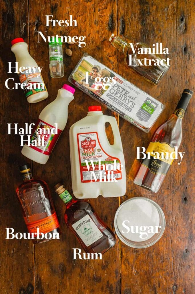 The ingredients for homemade eggnog are all laid out on a wooden tabletop.