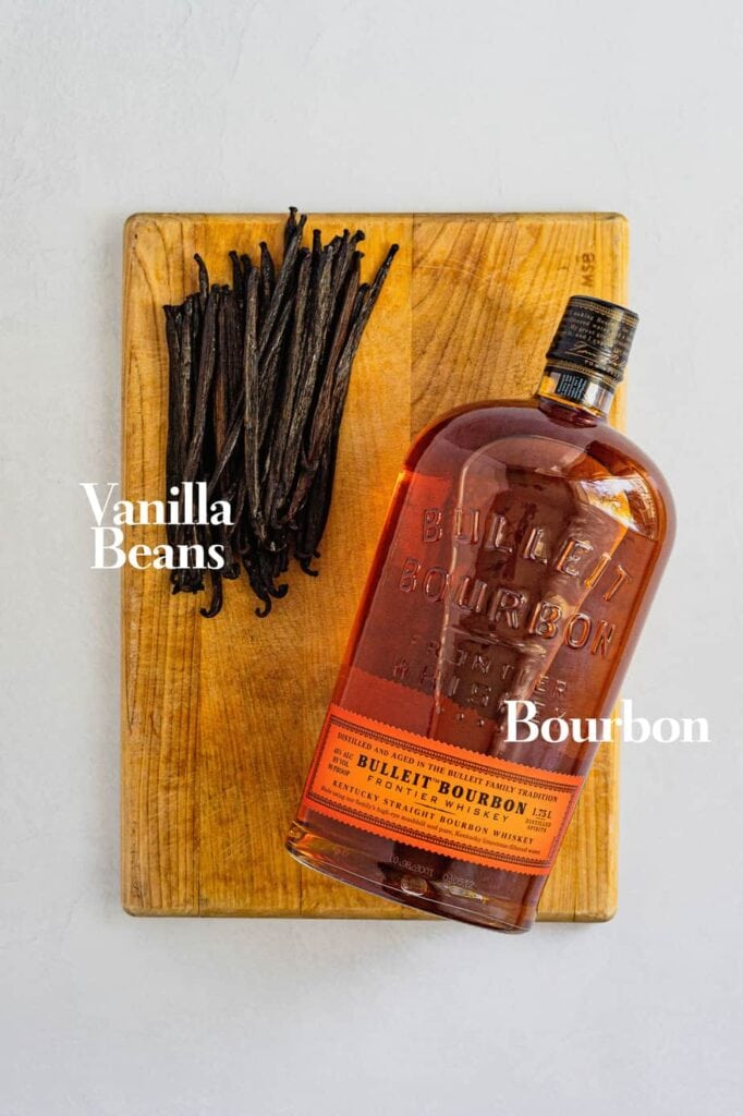 Vanilla beans and bourbon sit on a wooden cutting board. This is how to make homemade vanilla extract.