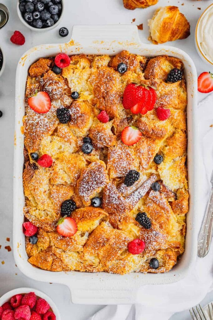 A white baking pan is filled with croissant french toast bake that is topped with powdered sugar and fresh berries. There are bowls of fresh berries and whipped cream surrounding the pan.