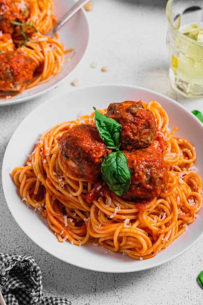 A large white bowl is full of spaghetti that is topped with venison meatballs and a sprig of fresh basil.