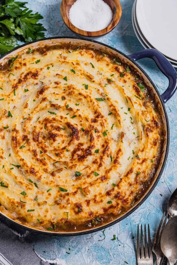 A shallow cast iron Dutch oven is filled with venison shepherd's pie. The top is sprinkled with parsley and the pan rests on a blue backdrop.