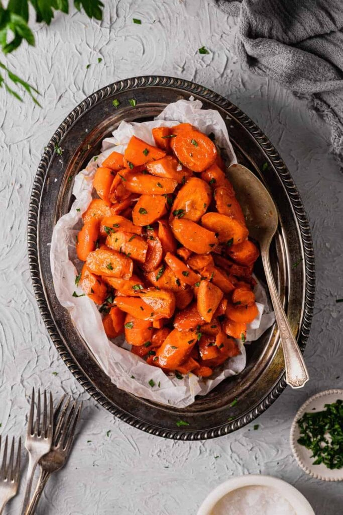 A large antique metal serving tray is filled with honey roasted carrots with cayenne pepper. There is a silver spoon in the dish and it sits on a textured grey backdrop.