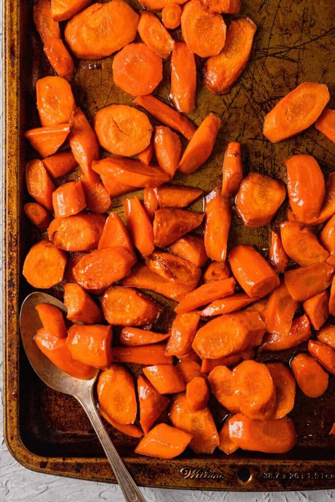 A baking tray filled with honey glazed roasted carrots. There is an antique silver spoon in the bottom left corner of the tray.