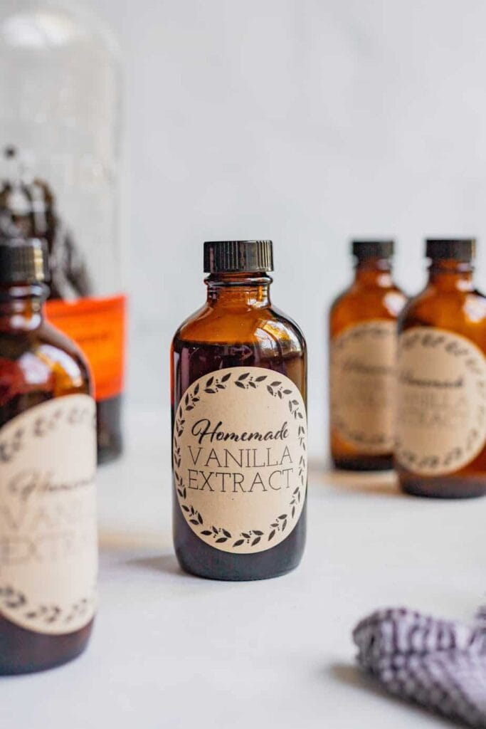 A collection of brown bottles filled with homemade vanilla extract that all have handmade labels on them.