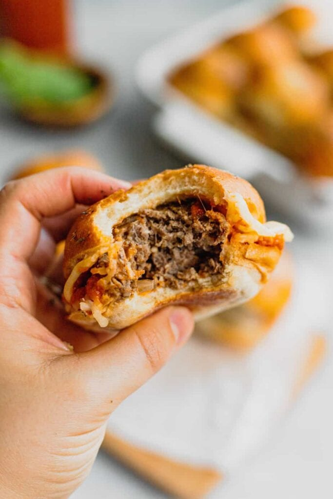 A hand holds a meatball slider with a bite taken out of it.