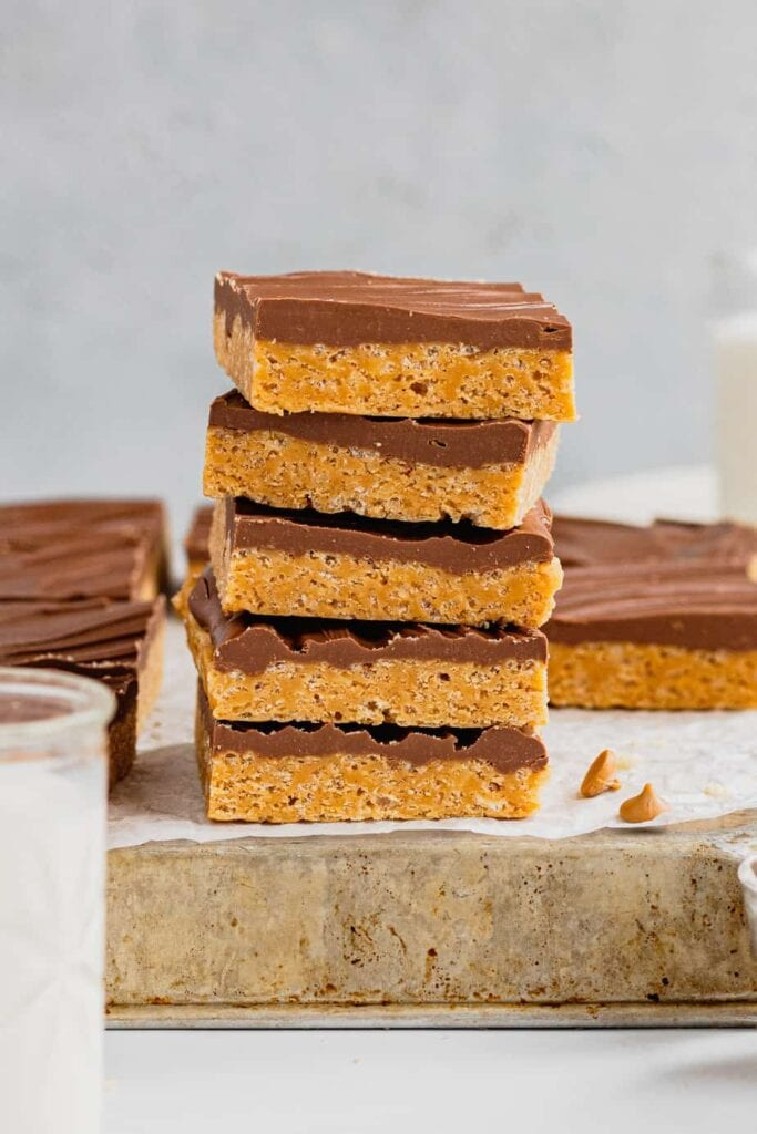 A stack of five slices of this O'Henry Bars recipe are on a piece of parchment paper on an overturned baking dish.
