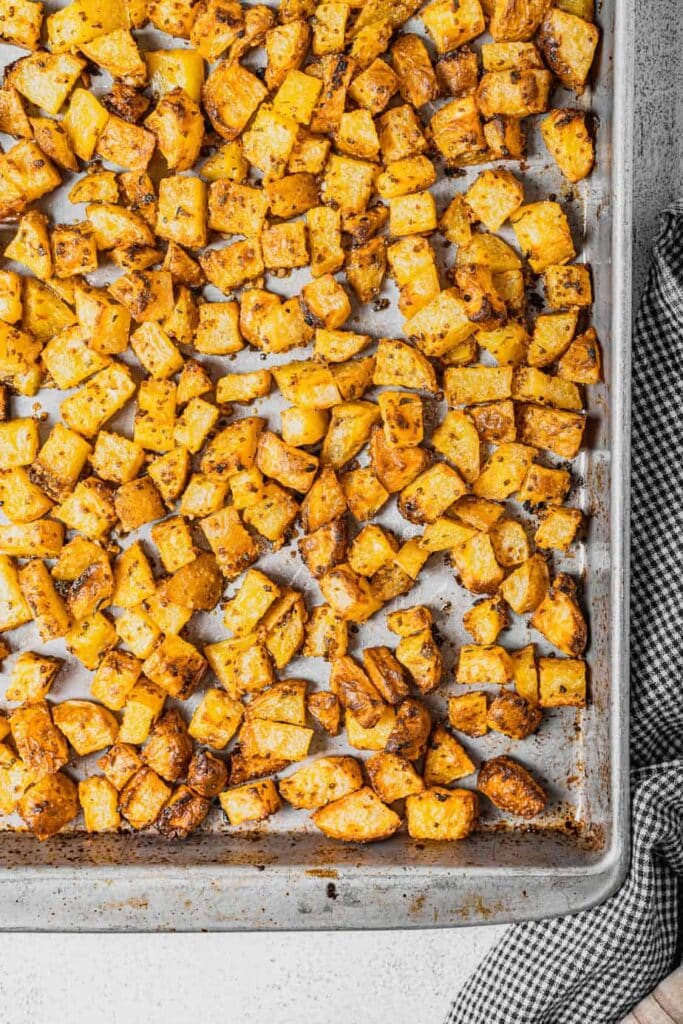 A silver rimmed baking tray is full of oven roasted potatoes with rosemary and mustard. There is a checkered napkin next to the pan.