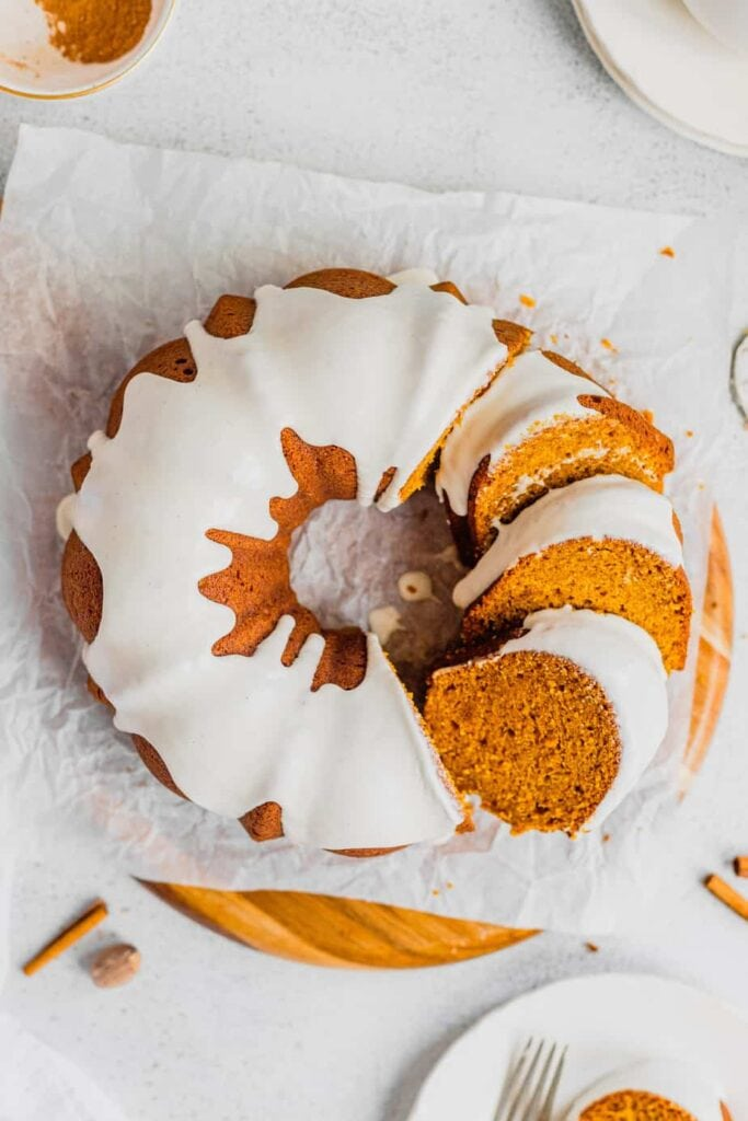 An overhead shot of slices of pumpkin spice cake layered over one another against the rest of the bundt cake. The whole thing is on a piece of parchment paper set on a wooden cutting board.
