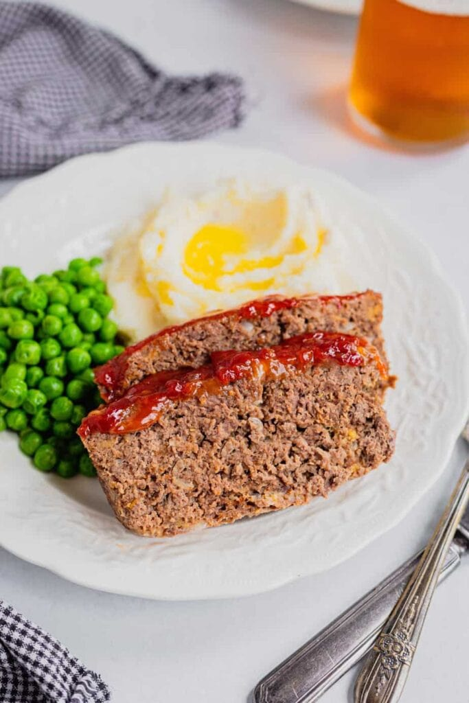 Two slices of venison meatloaf sit on a white plate with buttery mashed potatoes and green peas.