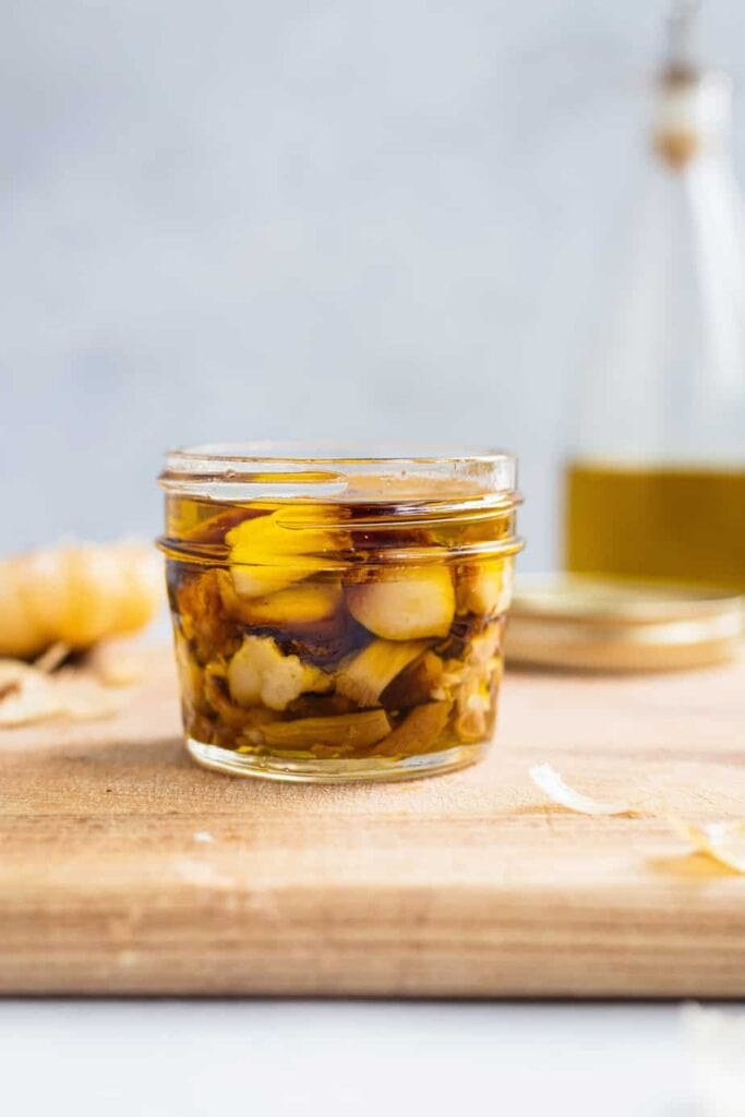 Cloves of roasted garlic are stored in a small glass jar covered in olive oil. The jar sits on a wooden cutting board.