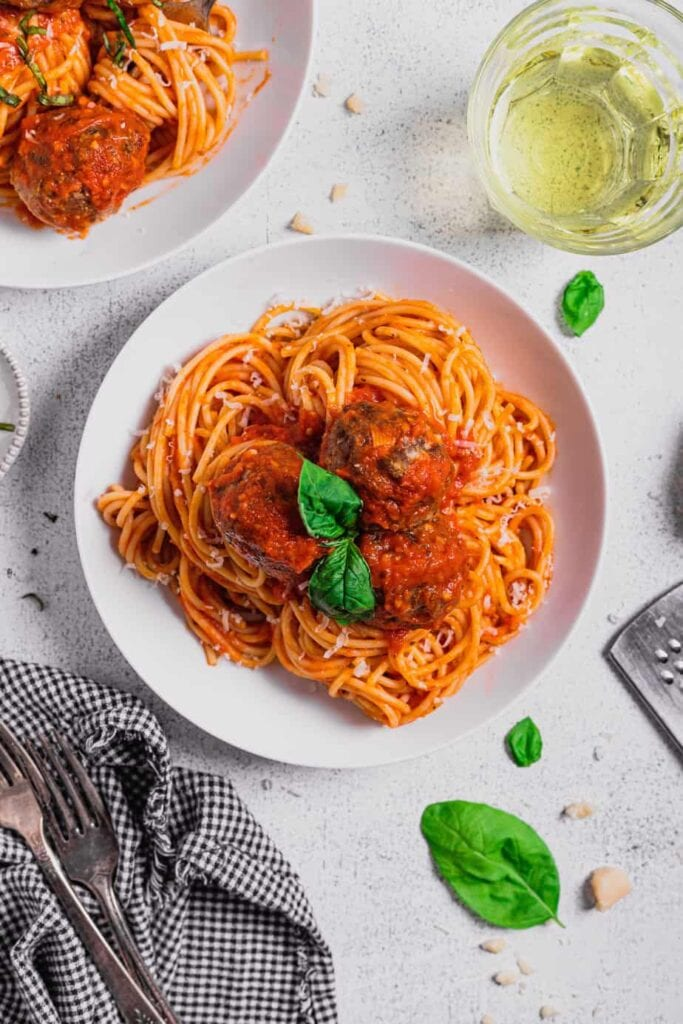 An overhead shot of a white plate filled with spaghetti and topped with venison meatballs recipe and a sprig of basil.