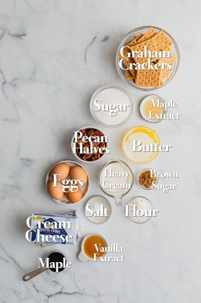 The ingredients for pecan pie cheesecake bars are arranged in various glass bowls and measuring cups on a white marble backdrop.