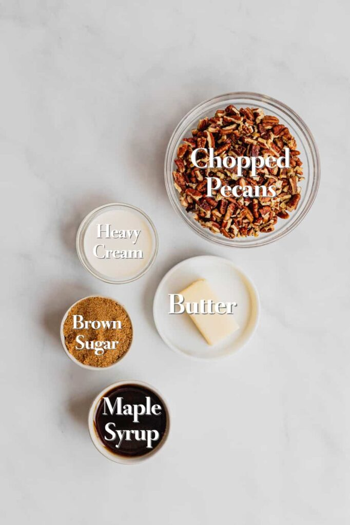 The ingredients for the pecan pie topping sit in various glass bowls and measuring cups on a marble backdrop.